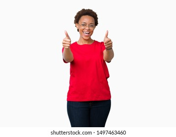 Beautiful young african american woman wearing glasses over isolated background approving doing positive gesture with hand, thumbs up smiling and happy for success. Looking at the camera