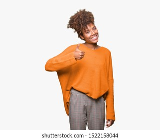 Beautiful young african american woman over isolated background doing happy thumbs up gesture with hand. Approving expression looking at the camera with showing success.
