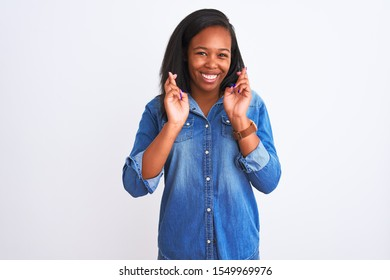 Beautiful young african american woman wearing denim jacket over isolated background gesturing finger crossed smiling with hope and eyes closed. Luck and superstitious concept.