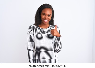 Beautiful young african american woman wearing winter sweater over isolated background doing happy thumbs up gesture with hand. Approving expression looking at the camera showing success.