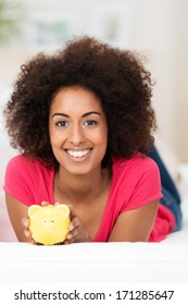 Beautiful young African American woman with a curly afro hairstyle with a piggy bank lying on a comfortable sofa looking at the camera with a warm friendly smile