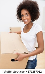 beautiful young African American woman with a curly afro hairstyle moving house carrying a brown cardboard carton and smiling at the camera