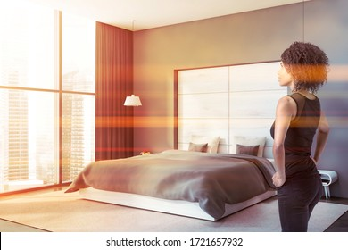 Beautiful young African American woman standing in panoramic bedroom with grey and wooden walls, concrete floor and comfortable king size bed. Window with blurry cityscape. Toned image