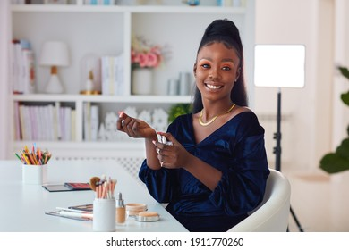 beautiful young african american woman applying a perfume fragrance at home, beauty blogger