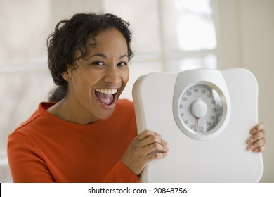 Beautiful young African American woman holding scale and shouting for joy