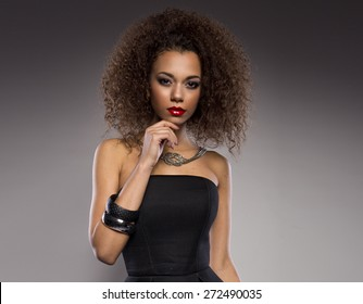 Beautiful young African American woman with afro in a fresh dark short summer dress posing holding up one edge of the flared skirt with a provocative expression, on a dark grey background