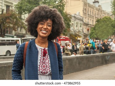 beautiful young African American woman smiling with an afro hairstyle and good sense of humor.  looking happy and relaxed.