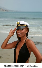 a beautiful young african american woman wears a sea captains hat while enjoying a day at the beach