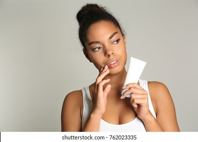 Beautiful young African American woman holding bottle with cream on light background