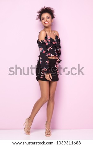 5a5fa2e72f7 Beautiful young african american woman with afro hairstyle posing on pink  pastel background wearing fashionable floral dress. Girl smiling
