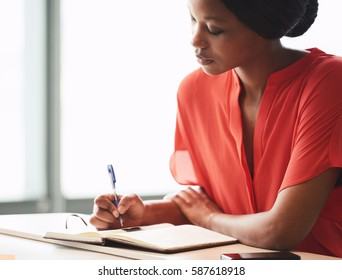 Beautiful young african american writer busy making hand written notes while wearing a bright orange blouse and sitting next to large bright windows.