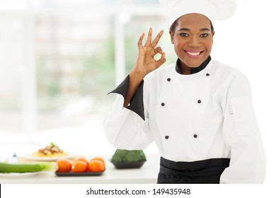 beautiful young african chef in hotel kitchen giving ok sign