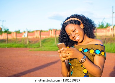 beautiful young african lady smiling while using her phone outdoors