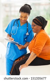 beautiful young african nurse explaining medical test result to senior patient