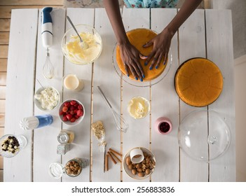 Beautiful young african woman cooking cake at kitchen. Top view