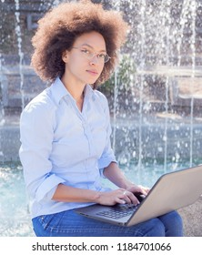 Beautiful Young African Woman With Curly Hair Using Laptop, Outdoor Portrait , Casual Wear , Looking At The Camera