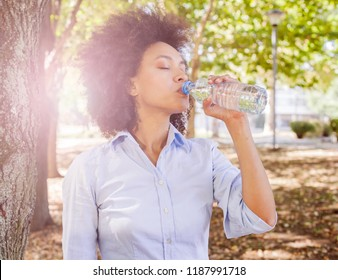 Beautiful young african woman drinking water from bottle and relaxing in nature , wear casual clothes, sunlight flare in background
