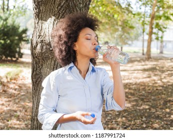 Beautiful young african woman drinking water from bottle and relaxing in nature , wear casual clothes, carefree outdoor lifestyle