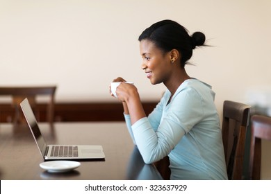 beautiful young african woman drinking coffee while using laptop at home