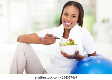 beautiful young african woman eating vegetable green salad