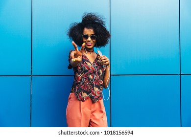 Beautiful young african woman in eyeglasses showing peace sign, listening to music in earphones, using a smartphone, Dressed in fashionable blouse and pants. Outdoors.