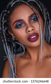 Beautiful young African woman with fashion makeup on black