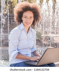 Beautiful Young African Woman With Glasses Working With Laptop. Outdoor Portrait , Casual Wear , Looking At The Camera