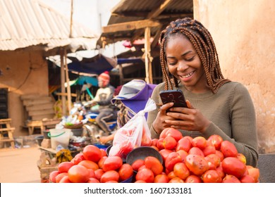 beautiful young african woman in a local african market viewing content on her phone smiling