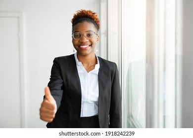 beautiful young african woman in office with hand gesture
