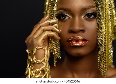 Beautiful young african woman posing at studio in golden jewellery, face with hand portrait over dark background