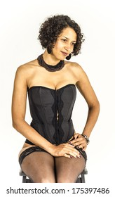 Beautiful young African woman sitting on a chair in black lace lingerie and stockings