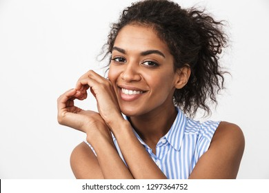 Beautiful young african woman standing over white background, showing love gesture