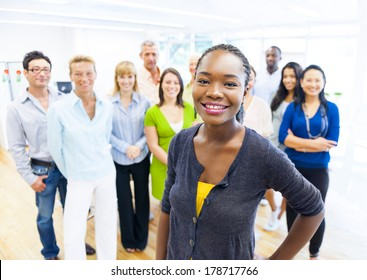 Beautiful Young African Woman Standing Out of the Crowd in Office