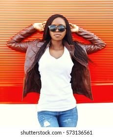 Beautiful young african woman in sunglasses and jacket at city over red background
