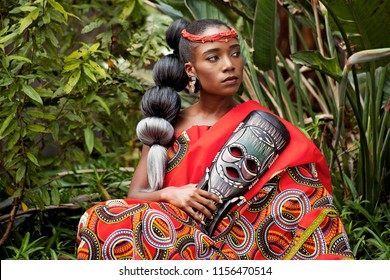 Beautiful young African woman wearing traditional clothing and holding a mask while sitting outside with foliage in the background