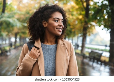 Beautiful young african woman wearing coat walking outdoors at the park, carrying backpack