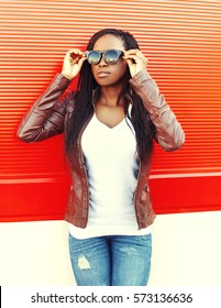 Beautiful young african woman wearing a jacket, sunglasses in city over red background