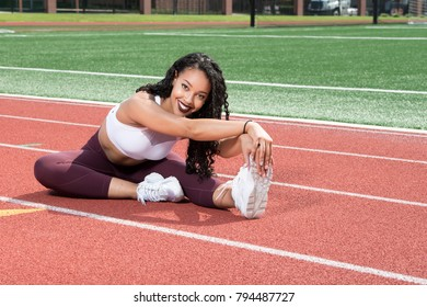 Beautiful young African-American fitness model stretches her legs while on an outdoor track