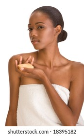 Beautiful young African-American woman with Slicked Back Hair wrapped in white bath towel an holding bar of soap preparing for sauna