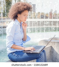 Beautiful Young Afro American Student Woman With Glasses Working With Laptop. Outdoor Portrait , Casual Wear , Looking At The Computer