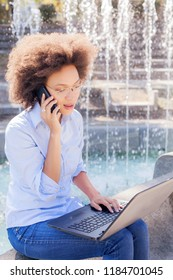 Beautiful Young Afro American Student Woman With Glasses Working With Laptop And Speaking By Phone. Outdoor Portrait , Casual Wear