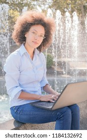 Beautiful Young Afro-American Student Woman With Curly Hair Working With Laptop. Outdoor Portrait , Casual Wear , Looking At The Camera