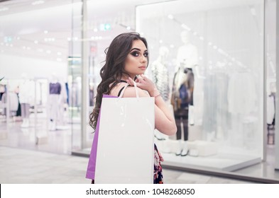 Beautiful young Arab woman shopping in a shopping mall, white bag over her shoulders and looking at camera,back view