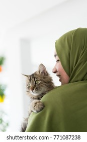 Beautiful young Arabic female indoors playing with cat