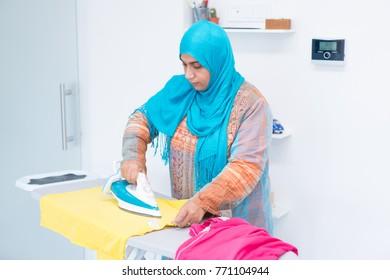 Beautiful young Arabic female indoors ironing