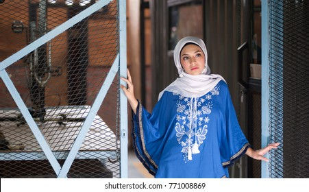 Beautiful young arabic girl in hijab posing for a camera on rustic background. Hijab fashion portraiture.