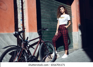 Beautiful young arabic woman with black curly hairstyle. Arab girl in casual clothes in the street near a bicycle. Girl power concept.