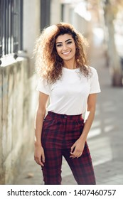 Beautiful young arabic woman with black curly hairstyle. Arab girl in casual clothes in the street. Happy female wearing white t-shirt and checked pants.
