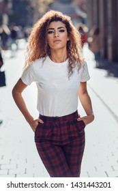 Beautiful young arabic woman with black curly hairstyle. Arab girl in casual clothes in the street. Girl power concept.