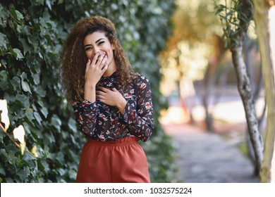 Beautiful young arabic woman laughing in urban background. Arab girl, black curly hairstyle,  wearing casual clothes in the street.